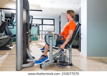 Hip abduction blond man exercise at gym indoor opening legs workout - stock photo