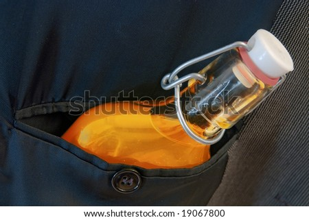 hip flask with elixir in breast pocket - stock photo