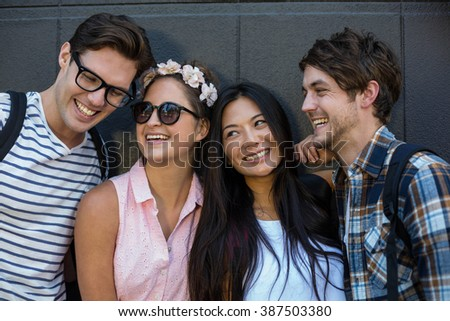 Hip friends smiling and leaning against wall