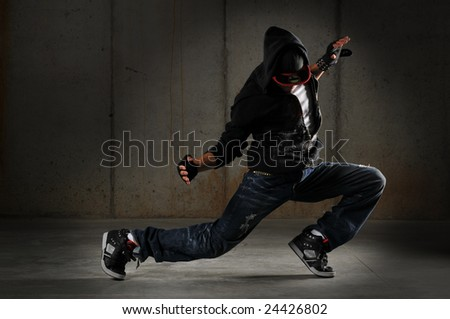 Hip hop dancer performing against a grunge wall - stock photo