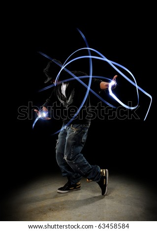 Hip Hop Dancer performing showing traces of lights against a dark background