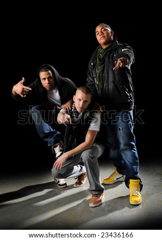 Hip hop dancers posing over a dark background - stock photo
