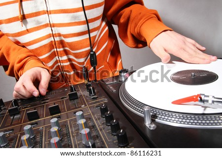 Hip hop DJ scratching vinyl records with music on turntable record player. Professional audio equipment for party,studio,concert. Male disc jockey model in orange coat,focus on crossfader and hands
