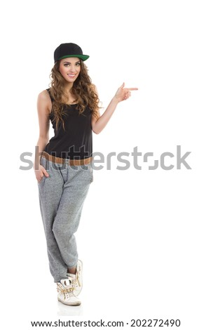 Hip hop girl pointing. Young woman in gray track-suit, black top and full cap pointing. Full length studio shot isolated on white. - stock photo