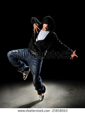 Hip hop style dancer with hood over a dark background with spotlight - stock photo