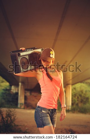 Hip hop woman with a cap which holding a tape recorder on shoulder. Toned image. - stock photo