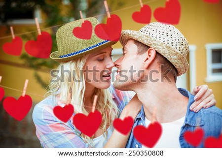 Hip young couple about to kiss against hearts hanging on a line - stock photo