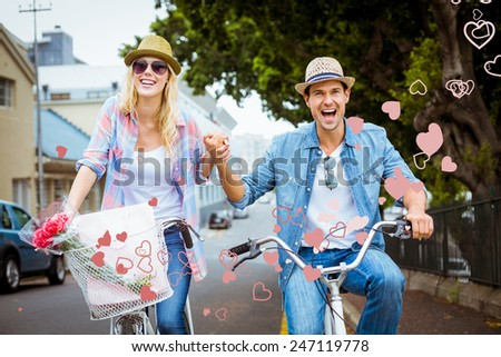 Hip young couple going for a bike ride against valentines heart design - stock photo