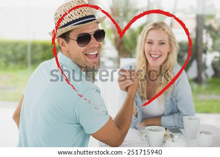 Hip young couple having coffee together against heart - stock photo