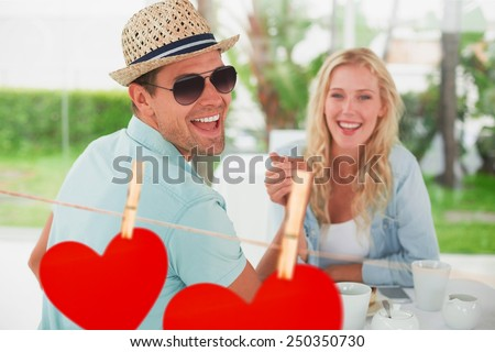 Hip young couple having coffee together against hearts hanging on a line - stock photo