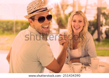 Hip young couple having coffee together on the cafe terrace on sunny day - stock photo