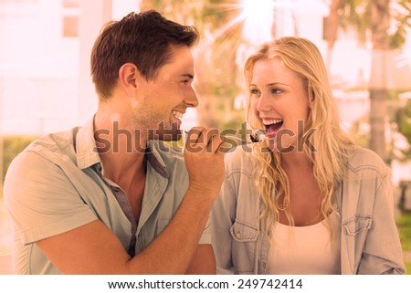 Hip young couple having desert together on the cafe terrace on sunny day