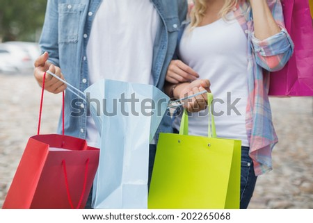 Hip young couple holding shopping bags on a sunny day in the city
