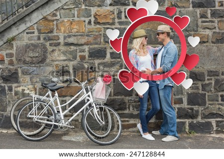 Hip young couple hugging by brick wall with their bikes against hearts - stock photo