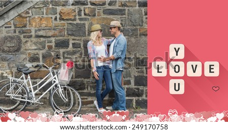 Hip young couple hugging by brick wall with their bikes against love you tiles - stock photo