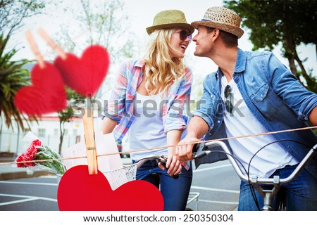 Hip young couple on a bike ride against hearts hanging on a line - stock photo