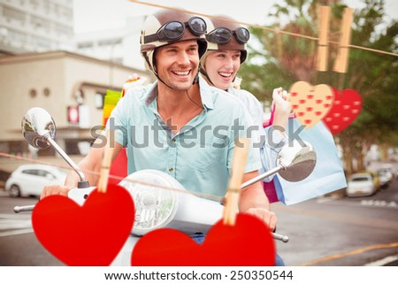Hip young couple riding scooter with shopping bags against hearts hanging on the line - stock photo
