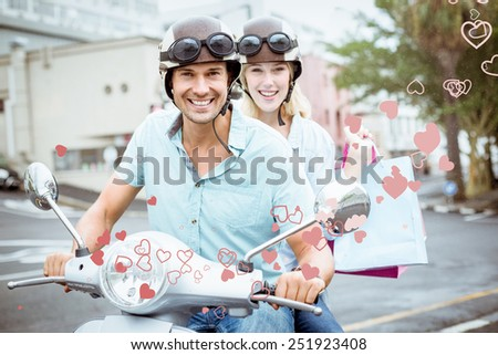 Hip young couple riding scooter with shopping bags against valentines heart design - stock photo