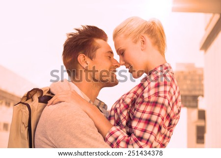 Hip young couple smiling at each other on a sunny day in the city - stock photo
