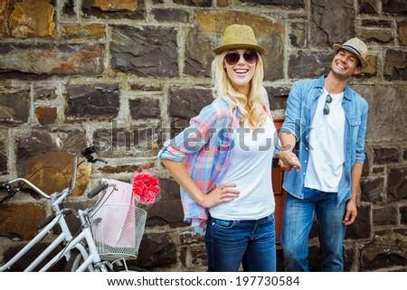 Hip young couple standing by brick wall with their bikes on a sunny day in the city - stock photo