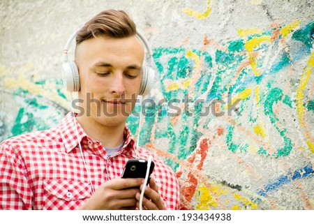 Hip young man listening to music downloaded on his MP3 player standing wearing a set of headphones in front of a grungy graffiti covered wall - stock photo