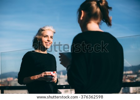 Hip young women talking in roof top cafe - stock photo
