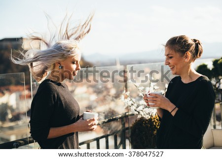 Hip young women talking in roof top cafe on windy day