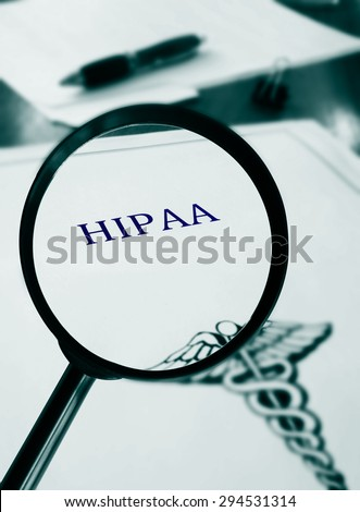 HIPAA document with magnifying glass                                - stock photo