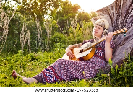 Hippie ethnic girl singer with guitar in the nature - stock photo