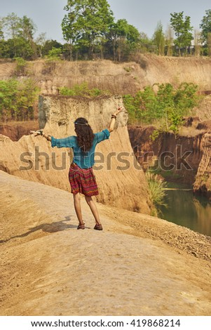 hippie girl dancing on cliff.