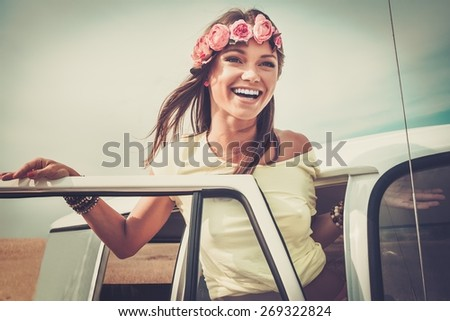 Hippie girl in a van on a road trip - stock photo