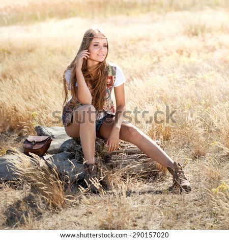 Hippie girl sitting on a tree stump - morning outdoors shot - stock photo