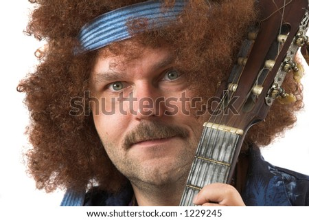 Hippie with a slightly crazy look holding his guitar (text on shirt is not a brandname) - stock photo