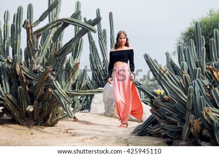 Hippie woman in long pink skirt walking near big cactuses - stock photo