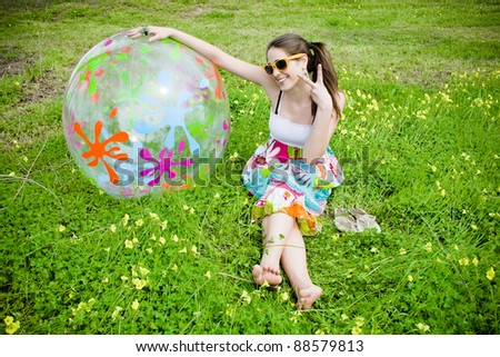 Hippie woman in the field of flowers with colored ball