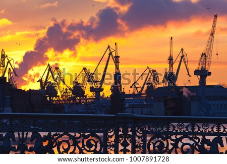 Hippocampus to the fence of the Blagoveshchensky bridge in St. Petersburg and harbor cranes in the background