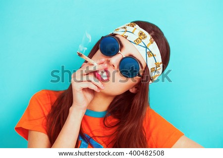 Hippy girl portrait smoking weed and wearing sunglasses - stock photo