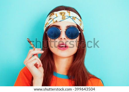 Hippy girl smoking weed and wearing sunglasses - stock photo