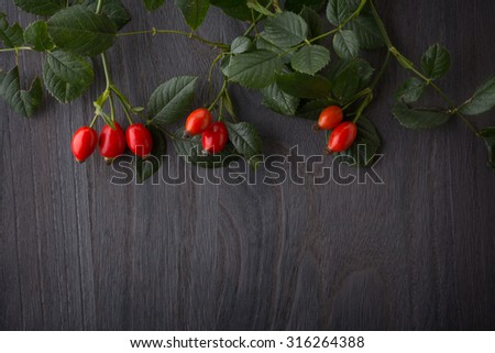 hips berries on rustic  wood  background - stock photo