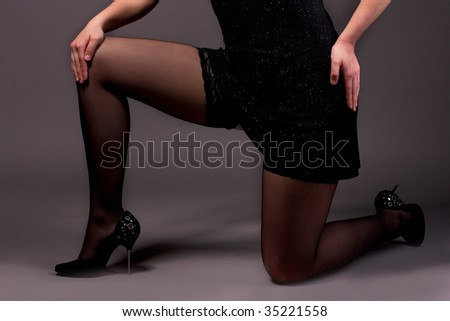 hips of young female in black dress isolated over gray
