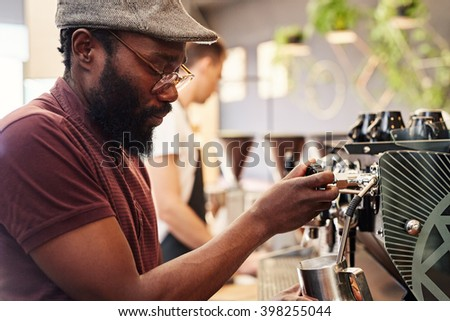 Hipster Afro man working an espresso machine in coffee shop - stock photo