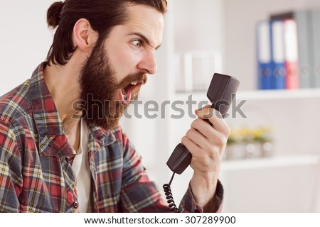 Hipster angry businessman making a call in his office - stock photo