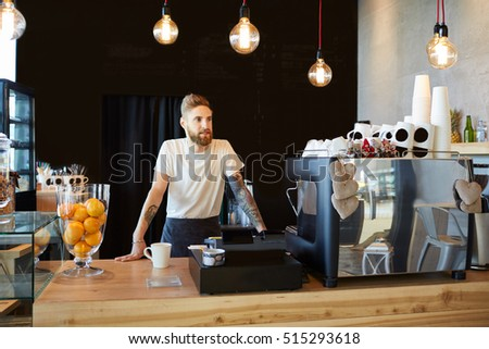 Hipster barista standing behind the bar at coffee shop