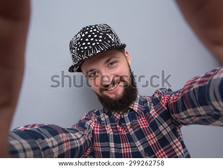 Hipster bearded man making selfies isolated on grey background. Handsome man in trucker hat smiling for the camera.