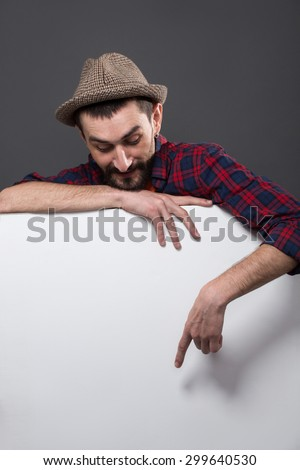 Hipster bearded man standing behind huge poster on dark grey. Smiling man with hat on showing smth on poster, text may be represented there. - stock photo