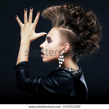 Hipster. Beauty woman with styling pigtails - iroquois, creative hairstyle, saluting Isolated on black - stock photo