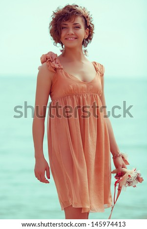 Hipster bride concept: portrait of a beautiful young woman with great tan wearing trendy wedding dress, posing and standing at the seaside. Girl holding bouquet. Outdoor shot