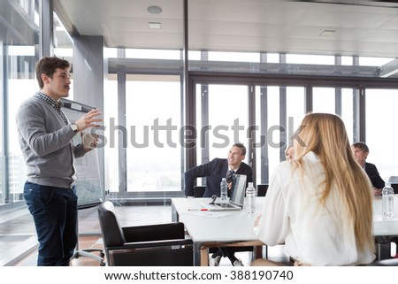 Hipster business man holding coffee cup and presenting the project in modern office. - stock photo