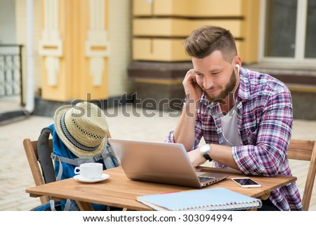 Hipster businessman drinking a cup of coffee in the city cafe during lunch time. He is working on laptop and calling by mobile phone. - stock photo