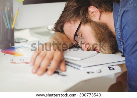 Hipster businessman sleeping at his desk in his office - stock photo